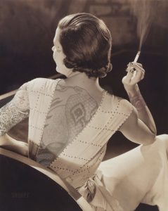 Portrait of a woman with her back to the camera with flower tattoos on her back and arms smoking a cigarette