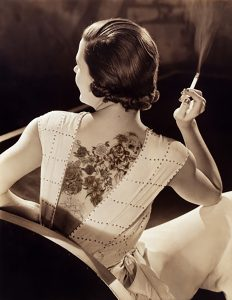 Portrait of a woman with her back to the camera with flower tattoos on her back smoking a cigarette